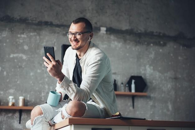 Kaukasischer geschäftsmann in weißer jeanskleidung benutzt ein telefon und kopfhörer, während er zu hause einen kaffee trinkt drinking