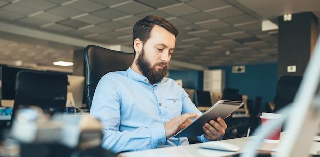 Kaukasischer geschäftsmann mit bart, der auf seinem tablett während der arbeit im büro sucht
