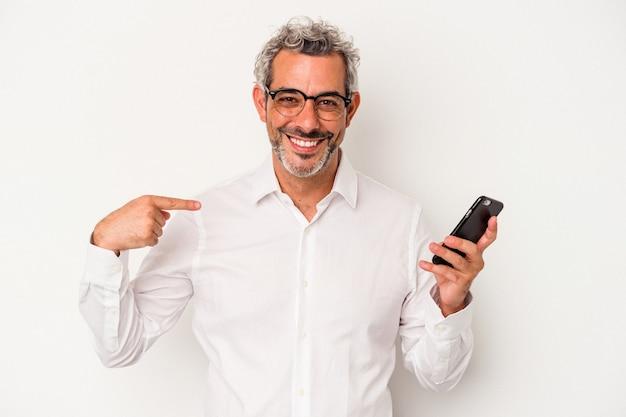 Kaukasischer geschäftsmann mittleren alters, der ein mobiltelefon einzeln auf weißem hintergrund hält, der mit der hand auf einen hemdkopierraum zeigt, stolz und zuversichtlich