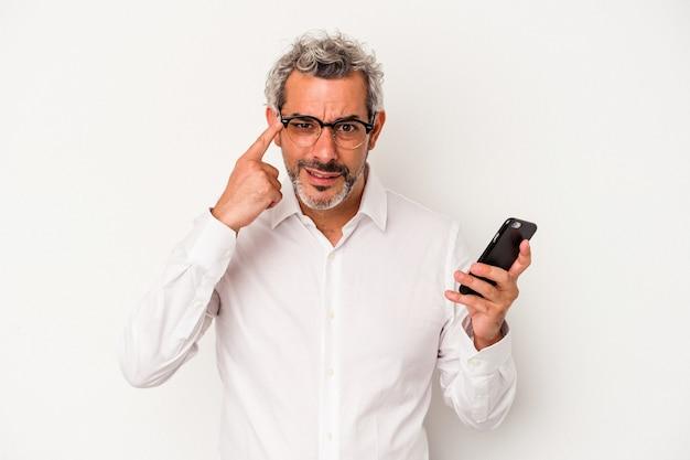 Kaukasischer geschäftsmann mittleren alters, der ein mobiltelefon isoliert auf weißem hintergrund hält und eine enttäuschungsgeste mit dem zeigefinger zeigt.