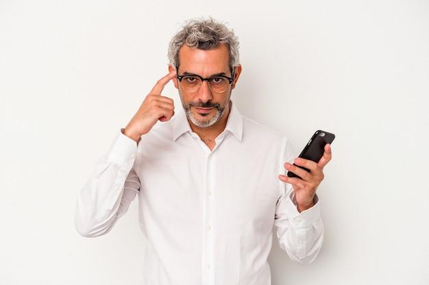 Kaukasischer geschäftsmann mittleren alters, der ein mobiltelefon isoliert auf weißem hintergrund hält und mit dem finger auf den tempel zeigt, denkt, konzentriert sich auf eine aufgabe.