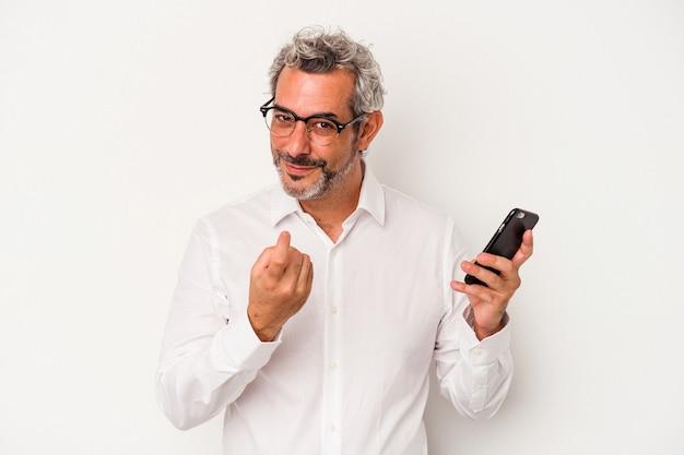 Kaukasischer geschäftsmann mittleren alters, der ein mobiltelefon isoliert auf weißem hintergrund hält und mit dem finger auf sie zeigt, als ob er einladen würde, näher zu kommen.