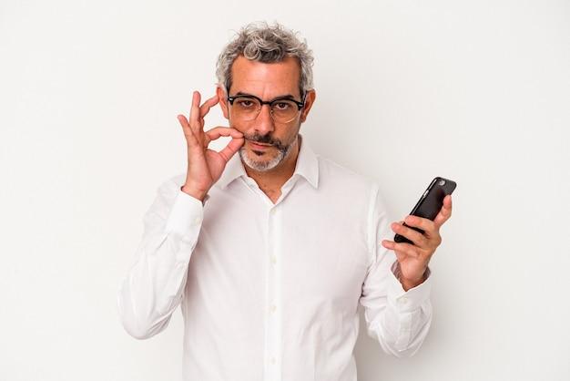 Kaukasischer geschäftsmann mittleren alters, der ein mobiltelefon lokalisiert auf weißem hintergrund mit fingern auf den lippen hält, die ein geheimnis halten.