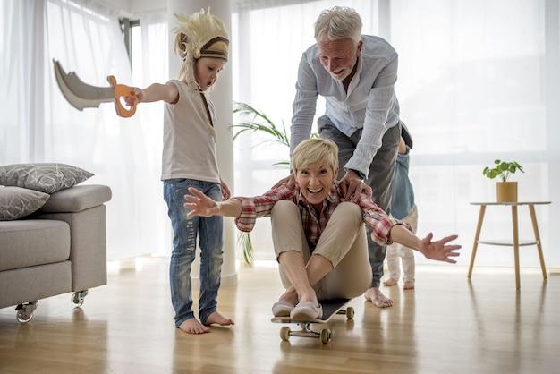 Kaukasischer großvater, der großmutter auf skateboard innen mit enkel drückt, der piratenkostüm trägt