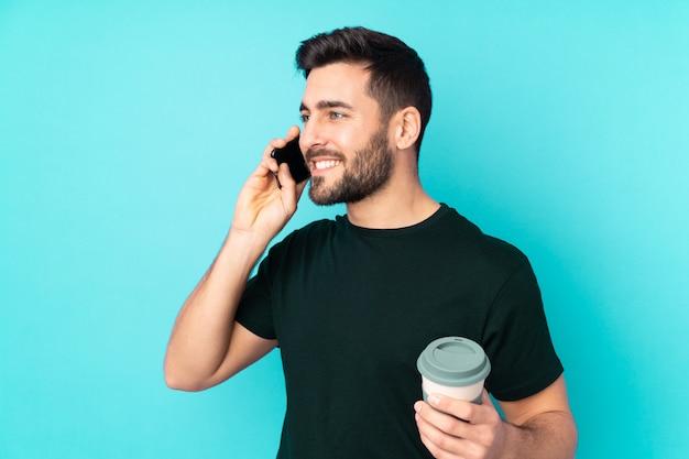 Kaukasischer gutaussehender mann auf blauer wand, die kaffee hält, um und ein handy wegzunehmen