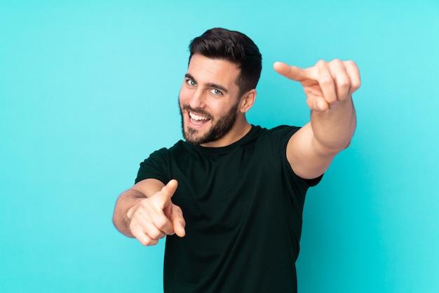 Kaukasischer gutaussehender mann auf blauer wand zeigt finger auf sie beim lächeln