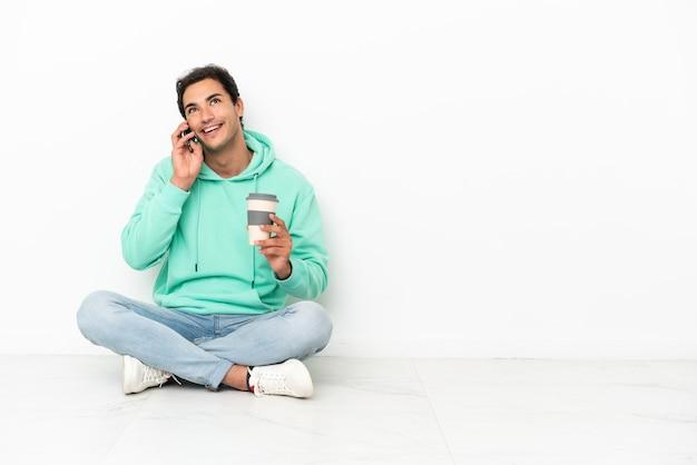 Kaukasischer gutaussehender mann, der auf dem boden sitzt und kaffee zum mitnehmen und ein handy hält