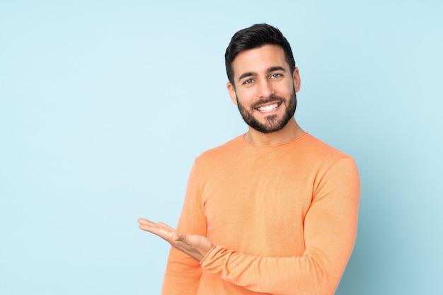 Kaukasischer gutaussehender mann, der eine idee präsentiert, während er über isolierte blaue wand lächelt