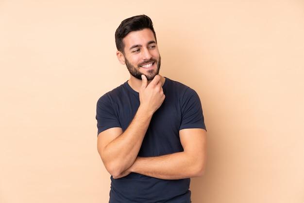 Kaukasischer gutaussehender mann lokalisiert auf beige wand, die zur seite schaut und lächelt