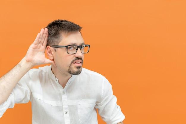 Kaukasischer gutaussehender mann mit brille über isoliertem hintergrund. ich versuche, eine hand-auf-ohr-geste zu hören, neugierig auf klatsch. hörproblem, taubes konzept. platz kopieren.