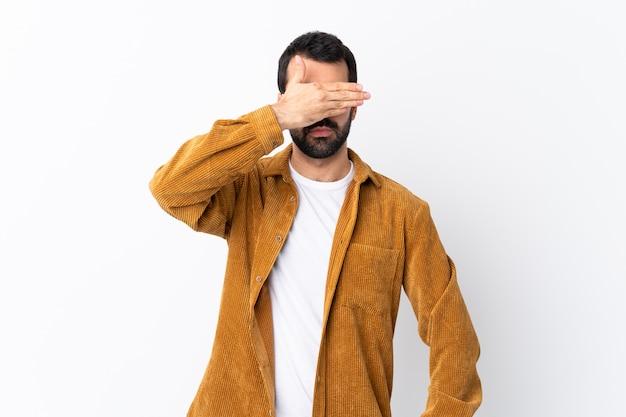 Kaukasischer gutaussehender mann mit dem bart, der eine kordjacke über lokalisierter weißer wandverkleidung trägt, mustert durch hände. ich will nichts sehen