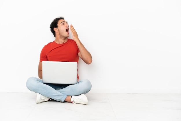 Kaukasischer gutaussehender mann mit einem laptop, der auf dem boden sitzt, gähnt und den weit geöffneten mund mit der hand bedeckt