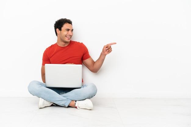Kaukasischer gutaussehender mann mit einem laptop, der auf dem boden sitzt, mit dem finger zur seite zeigt und ein produkt präsentiert