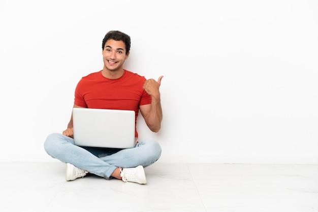 Kaukasischer gutaussehender mann mit einem laptop, der auf dem boden sitzt und auf die seite zeigt, um ein produkt zu präsentieren
