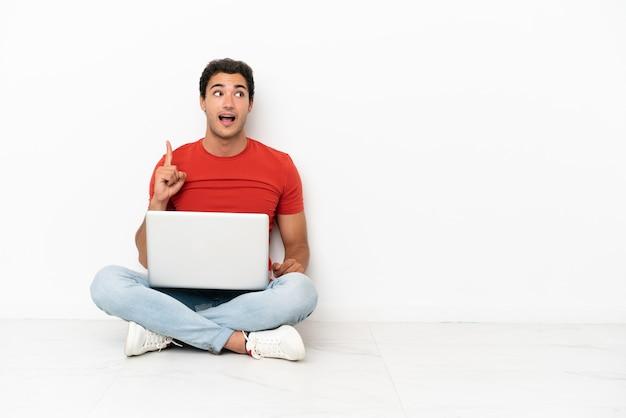 Kaukasischer gutaussehender mann mit einem laptop, der auf dem boden sitzt und beabsichtigt, die lösung zu realisieren, während er einen finger hochhebt