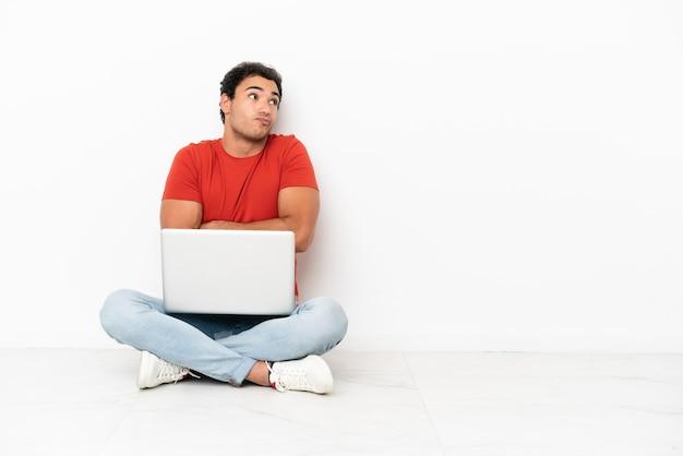 Kaukasischer gutaussehender mann mit einem laptop, der auf dem boden sitzt und beim anheben der schultern zweifel macht