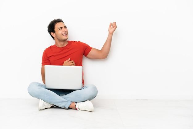Kaukasischer gutaussehender mann mit einem laptop, der auf dem boden sitzt und gitarrengeste macht