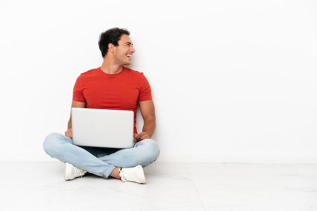 Kaukasischer gutaussehender mann mit einem laptop, der auf dem boden sitzt und in seitlicher position lacht