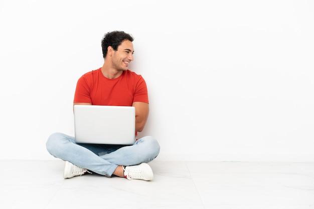 Kaukasischer gutaussehender mann mit einem laptop, der auf dem boden sitzt und seitlich schaut