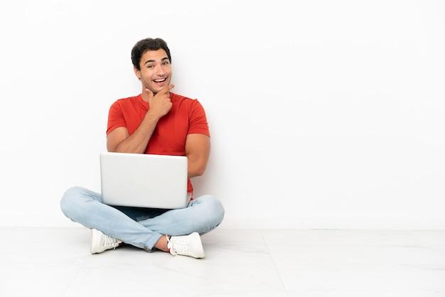 Kaukasischer gutaussehender mann mit einem laptop, der lächelnd auf dem boden sitzt