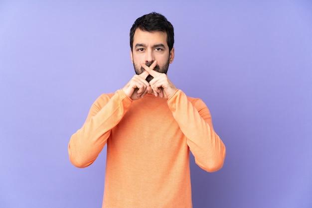 Kaukasischer gutaussehender mann über isoliertem purpur, der ein zeichen der stille geste zeigt