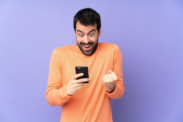 Kaukasischer gutaussehender mann über isoliertem purpur überrascht und eine nachricht sendend