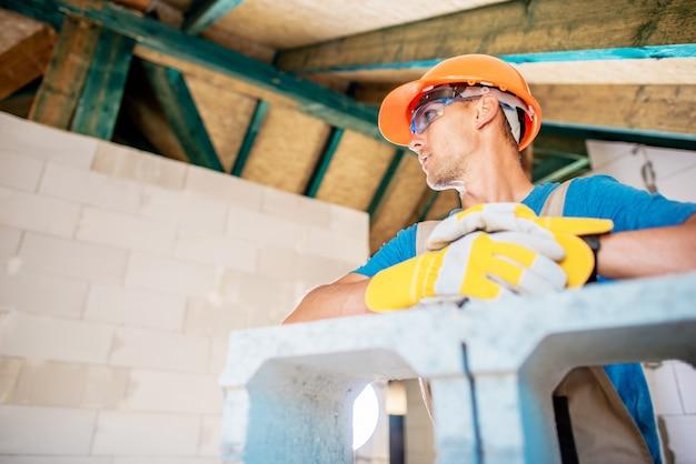 Kaukasischer hausbauarbeiter und errichtende betonblock-materialien
