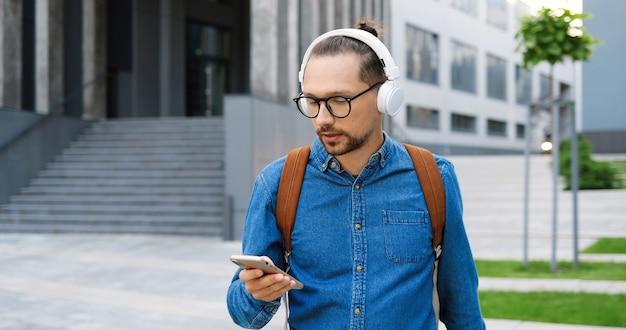 Kaukasischer hübscher junger mann in den gläsern, die kopfhörer aufnehmen und musik draußen an der stadtstraße hören. gut aussehender mann mit brille hört lied in der stadt. männlicher student mit rucksack.