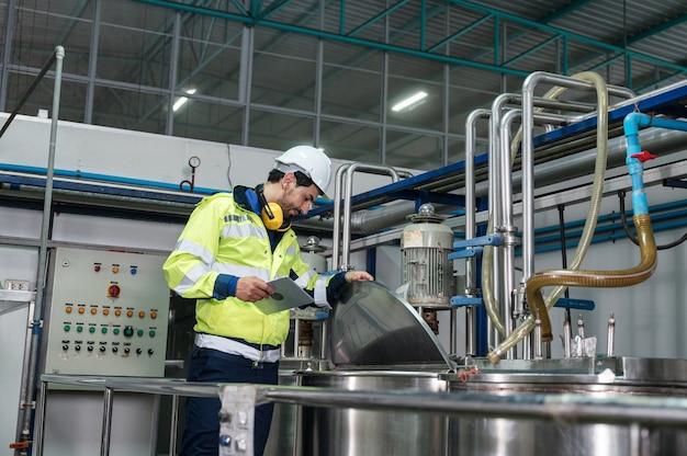 Kaukasischer ingenieur mann in uniform zu fuß, um kesseltanks mit flüssigkeitsleitung in der getränkefabrik zu überprüfen