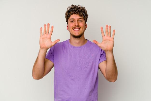 Kaukasischer jüngling lokalisiert auf weißem hintergrund, der nummer zehn mit den händen zeigt.