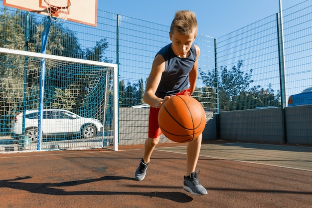 Kaukasischer jugendlichjungen-straßenbasketballspieler mit ball