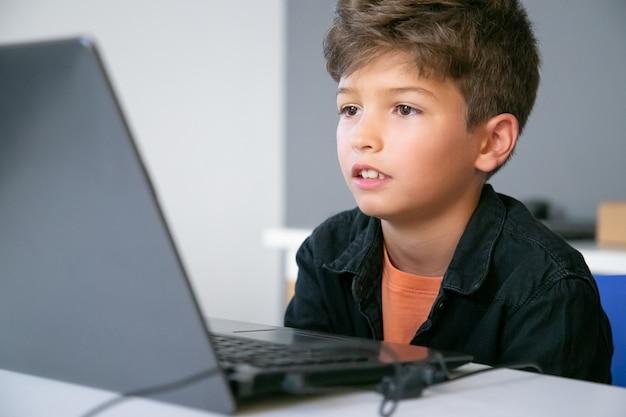 Kaukasischer junge, der am tisch im klassenzimmer sitzt, text auf dem bildschirm liest oder videopräsentation sieht