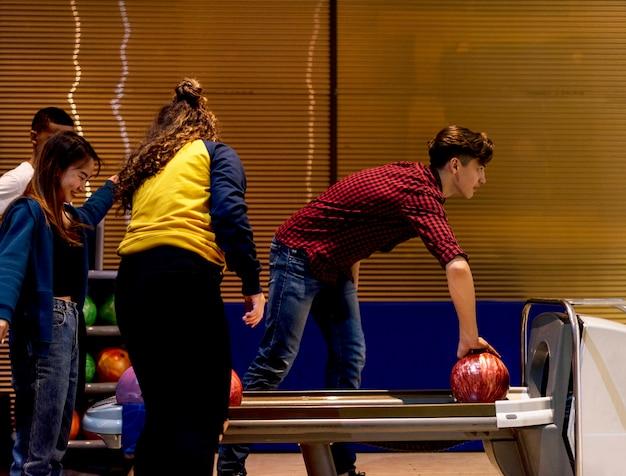 Kaukasischer junge, der ein bowlingkugelhobby- und -freizeitkonzept aufhebt