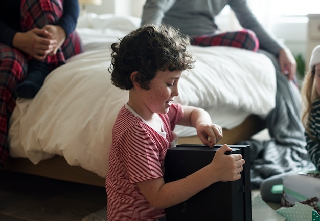 Kaukasischer junge, der ein weihnachtsgeschenk auspackt