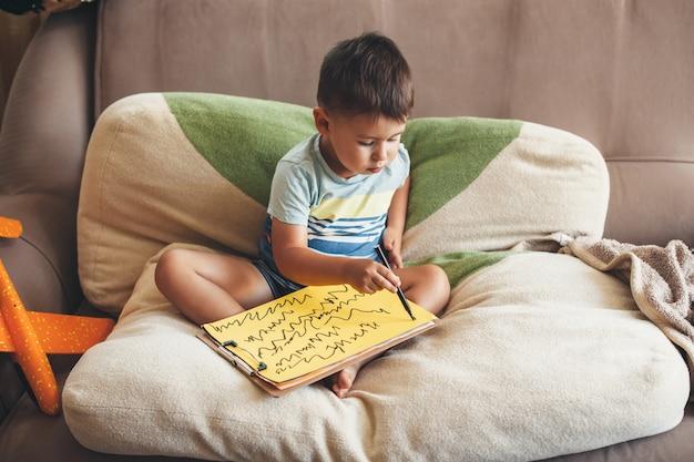 Kaukasischer junge, der etwas auf einem gelben papier mit einem marker zeichnet, während er im bett auf kissen sitzt