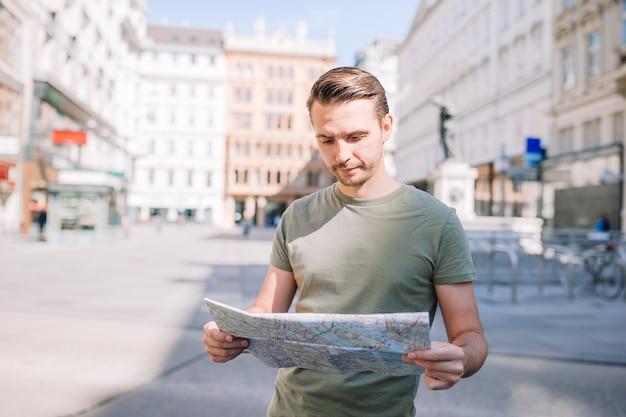 Kaukasischer junge, der karte der europäischen stadt betrachtet.