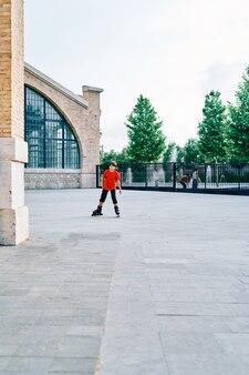 Kaukasischer junge, der mit rollschuhen im park spielt.