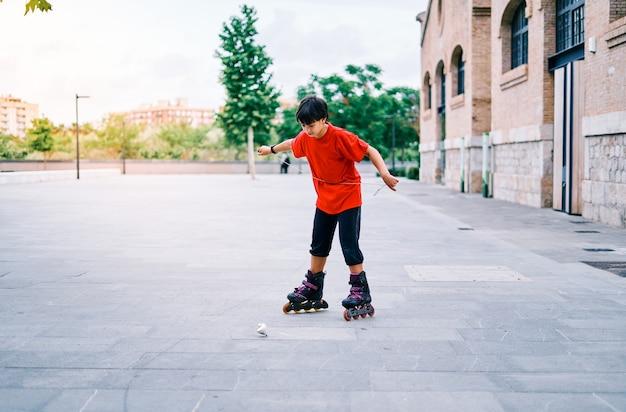 Kaukasischer junge, der mit rollschuhen spielt und kreisel im park wirft.