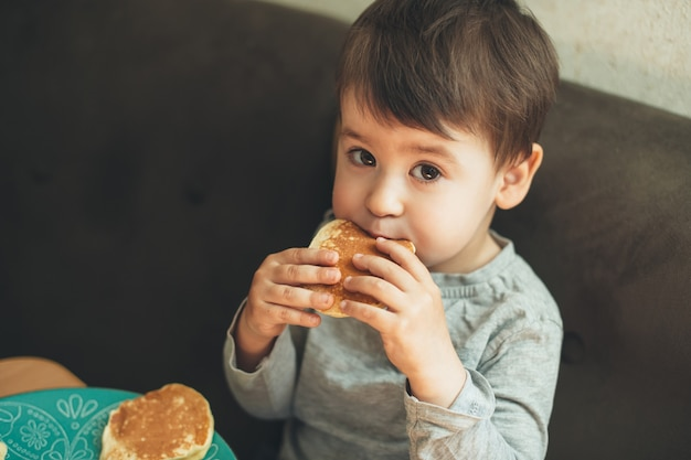 Kaukasischer junge, der oben kamera schaut, während köstliche kuchen zu hause isst
