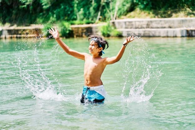 Kaukasischer junge im badeanzug, der im sommer mit flusswasser spielt.
