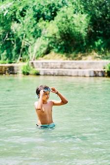 Kaukasischer junge im badeanzug mit wassergläsern im fluss im sommer