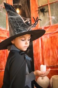Kaukasischer junge im farytalkarnevalszaubererkostüm, das in der hand kerze auf halloween-dekorhintergrund hält