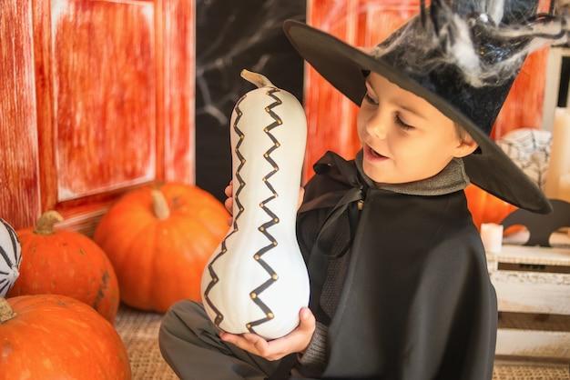 Kaukasischer junge im farytalkarnevalszaubererkostüm mit dekorativem kürbis auf halloween-dekorhintergrund