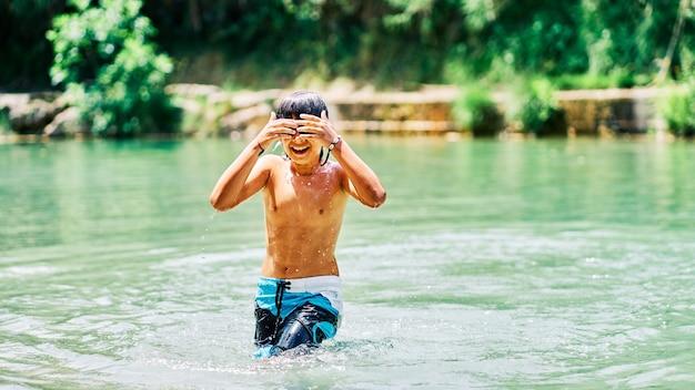 Kaukasischer junge in badehose im flusswasser im sommer