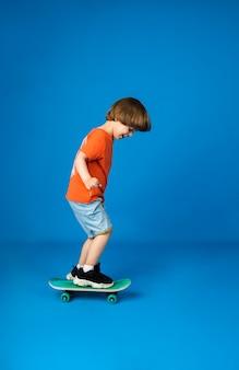 Kaukasischer junge mit braunen haaren in einem orangefarbenen t-shirt und jeansshorts reitet ein skateboard auf einer blauen oberfläche mit platz für text. sport für kinder