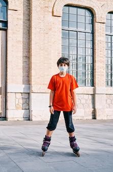 Kaukasischer junge mit maske, der mit rollschuhen im park spielt.