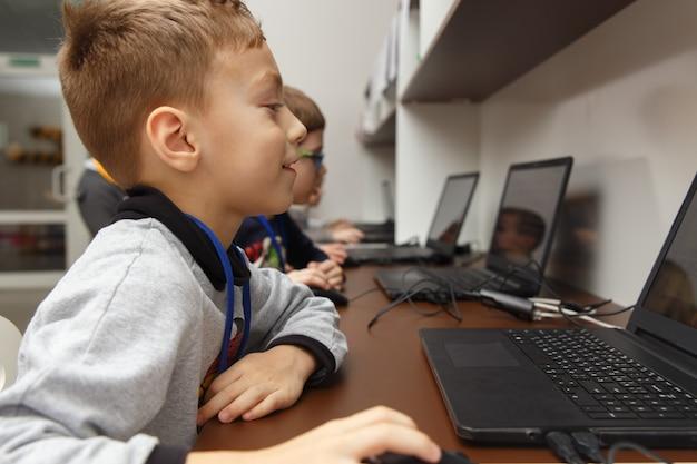 Kaukasischer junge mit seinen freunden, die lernen, einen computer an der schule der digitaltechnik zu benutzen