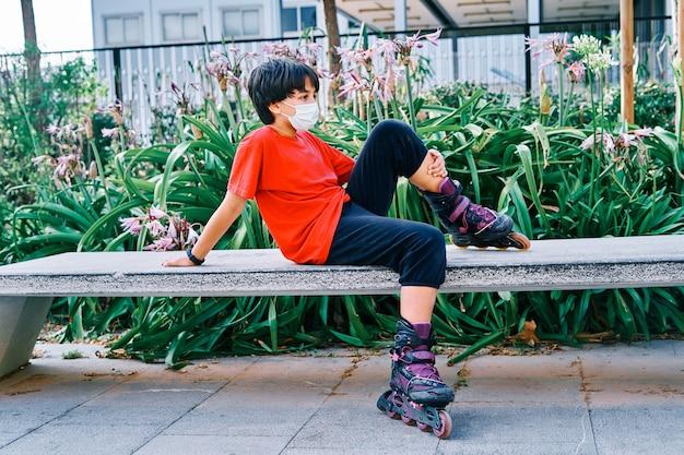 Kaukasischer junge sitzt auf einer bank mit rollschuhen im park.