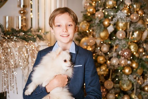Kaukasischer junge umarmt seinen geliebten hund auf dem hintergrund eines weihnachtsbaumes zu hause glückliches kind auf chri...