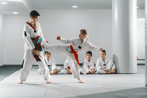 Kaukasischer junge und mädchen in doboks, die taekwondo-training im fitnessstudio haben. mädchen tritt, während junge trittziel hält.